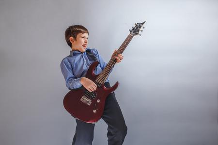 enthusiastically: boy adolescence European appearance enthusiastically playing gui Stock Photo