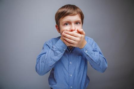 personas tristes: muchacho en una boca susto camisa cubierta con sus manos Foto de archivo