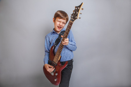boy playing guitar: boy playing guitar on gray background Stock Photo