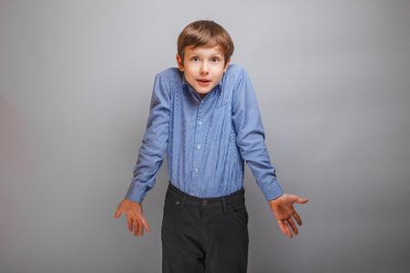 boy shrugs from ignorance surprised