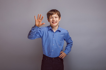 pre adolescent boy: boy teenager European appearance smiles and waves, joy Stock Photo