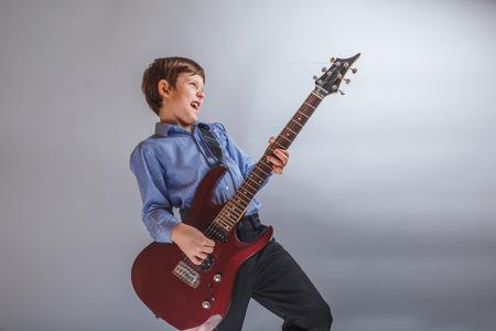 teenager boy brown hair European appearance playing guitar
