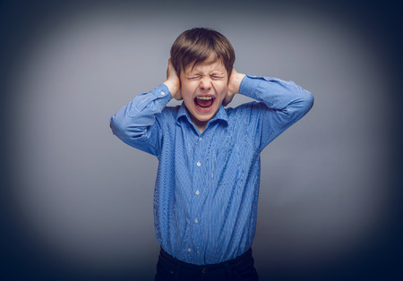 hands covering ears: teenager boy covering his ears screaming hands on a gray backgro