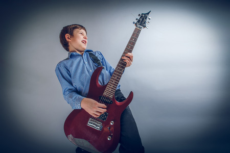 young musician: boy teenager European appearance brown emotionally plays guitar Stock Photo