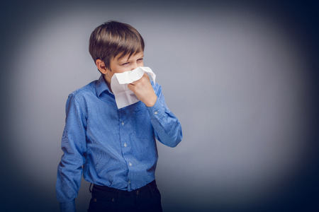 hanky: teenager boy of 10 years European appearance sick sneezing in Stock Photo