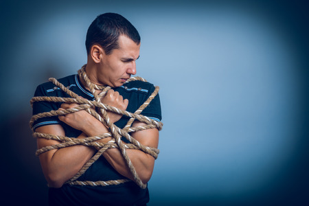the man of European appearance brunet tied with rope on a gray b photo