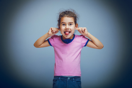 teases: child girl showing tongue pulls ears teases on a gray background