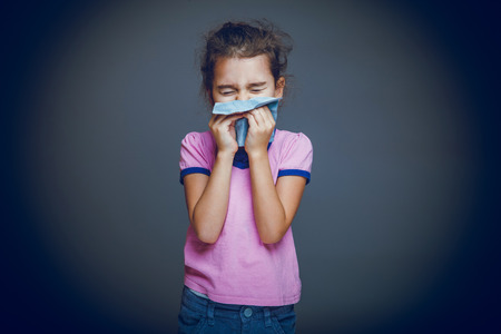 girl child sneezes into handkerchief on a gray background cros