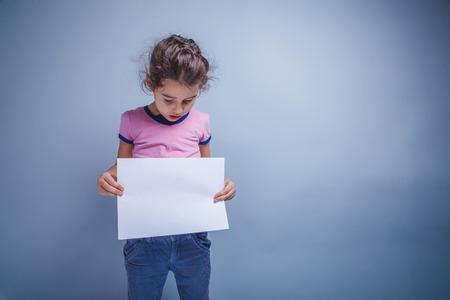 blank slate: girl child 6 years of European appearance holds a blank slate, l