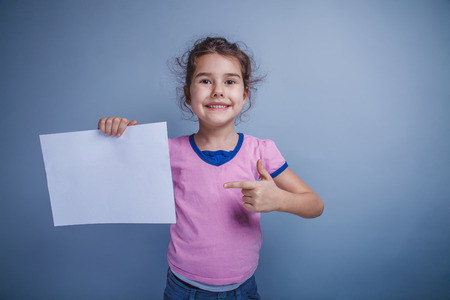 6 years: girl child 6 years of European appearance holds a clean sheet on Stock Photo