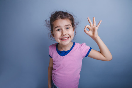 6 years: girl child 6 years of European appearance showing thumbs up