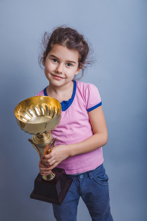 6 years: girl child 6 years of European appearance  holds  a cup