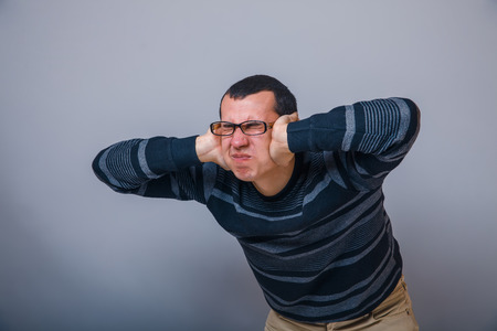 hands covering ears: European-looking male covering ears with his hands brunet on Stock Photo