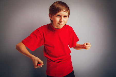 youth crime: European-looking boy of ten years holding a knife in his hand Stock Photo