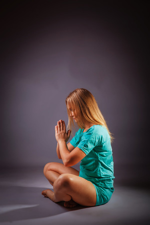 meditates: girl blonde European appearance in a blue tracksuit meditates on