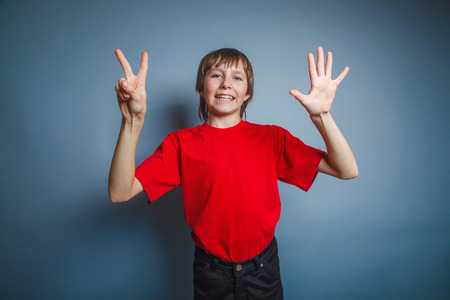 seven persons: European-looking boy of ten years shows the number seven finger Stock Photo