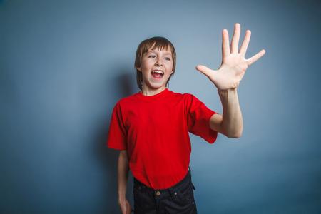 five fingers: European-looking boy of ten years shows a figure five fingers on
