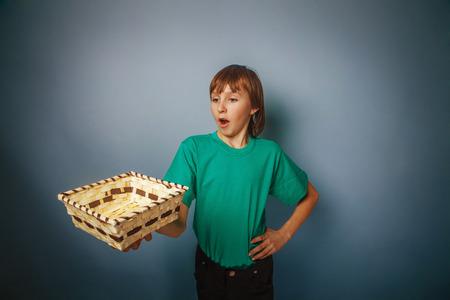 ten empty: European-looking  boy of  ten years  holding an empty basket in Stock Photo