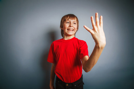 European-looking boy of ten years shows a figure four fingers on photo