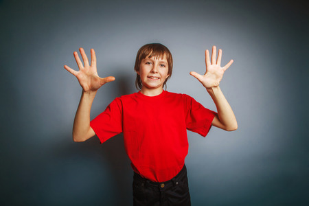 10 fingers: European-looking boy of ten years shows a figure ten fingers on Stock Photo