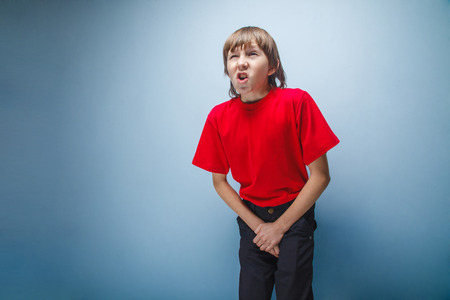 incontinence: Boy, teenager, twelve years in  red shirt wants to use  toilet, cystitis Stock Photo