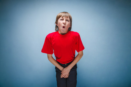 incontinence: Boy, teenager, twelve years in the red shirt wants to use the toilet, cystitis Stock Photo
