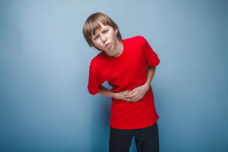 dolor de estomago: Muchacho adolescente de doce años en la camisa roja dolor abdominal, gastritis, diarrea