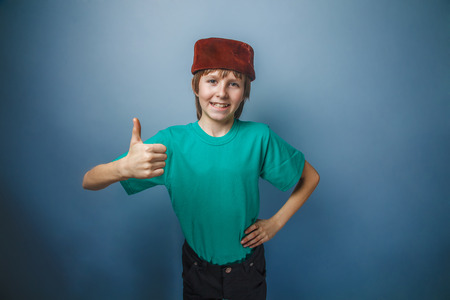 skullcap: Muslim boy of ten years, skullcap, thumbs up on a gray background