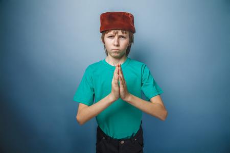 skullcap: Muslim boy of ten  years, skullcap, prayer on a gray background
