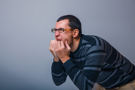 male of European appearance dark hair stuck his hands in his mouth on a gray background, nausea, vomiting Stock Photo