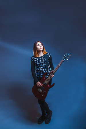 European-looking girl in a sweater holding a guitar and looking up on a gray background, sadness, grief, sadness photo