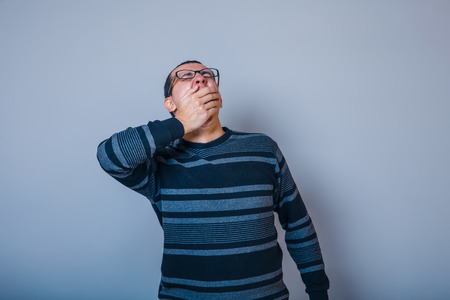 drowsiness: male European appearance brunet in sweater yawns covers her mouth on a gray background, drowsiness