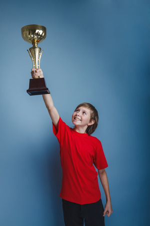 lifted hands: boy teenager European appearance in a red shirt lifted the cup in his hands on a gray background, the reward Stock Photo