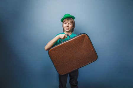 European-looking boy of ten years with a  suitcase in a hat  on a gray background photo