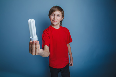 t bulb: boy teenager European appearance in a red shirt holding a light bulb in his hand, the idea of happiness