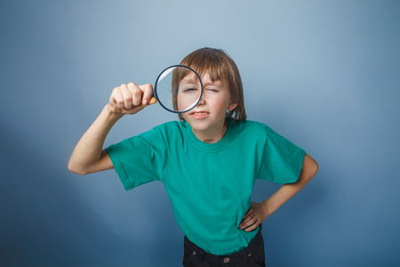 boy teenager European appearance in green t-shirt holding a magnifying glass on a gray background, knowledge photo