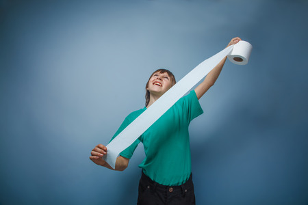 unwound: boy teenager European appearance in a green shirt holding unwound toilet paper on a gray background, mischief Stock Photo