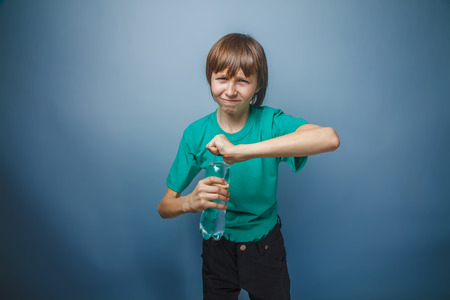 not open: ragazzo adolescente aspetto europeo in una T-shirt verde non pu� aprire una bottiglia su uno sfondo grigio, tristezza, risentimento Archivio Fotografico