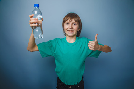 okey: boy teenager European appearance in a green t-shirt showing sign okey holding a bottle of water on a gray background Stock Photo