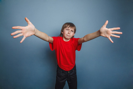 laying forward: boy, teenager, twelve years old, wearing a red shirt, stretched  forward his arms
