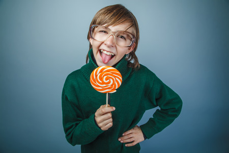 licking tongue: teenager boy brown hair European appearance in green sweater with glasses licking tongue candy on a gray background, sweet, retro Stock Photo