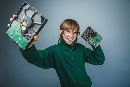 computer part: European appearance teenager boy with big glasses in a long green jumper holds a computers hard disks on a gray background, retro, computer technician
