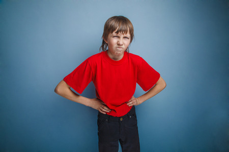 Boy, teenager, twelve years in the red shirt, hands in the side, angry Stock Photo
