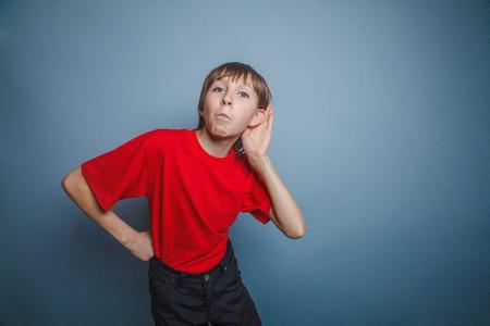 enclosing: Ragazzo, adolescente, dodici anni, in una camicia rossa, una mano dietro l'orecchio sua, intercettazioni Archivio Fotografico