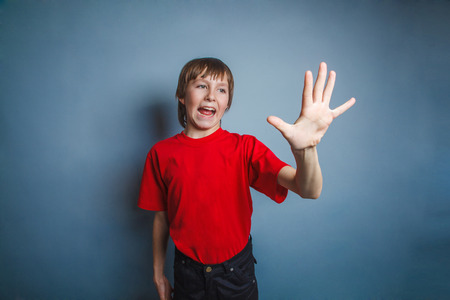 five to twelve: Boy, teenager, twelve years old, in a red shirt, showing a hand of five