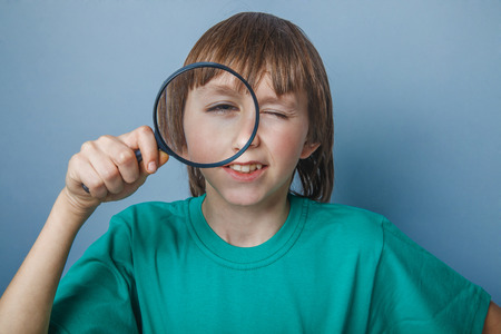 Boy, teenager, twelve years in a green t-shirt, looking through a magnifying glass with one eye photo