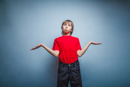 threw: Boy, teenager, twelve years in red T-shirt, threw up his hands, the unknow Stock Photo