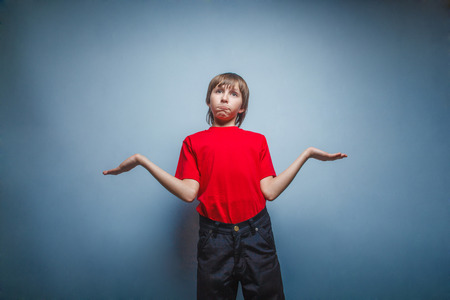 threw: Boy, teenager, twelve years in red T-shirt , threw up his hands, the unknown Stock Photo