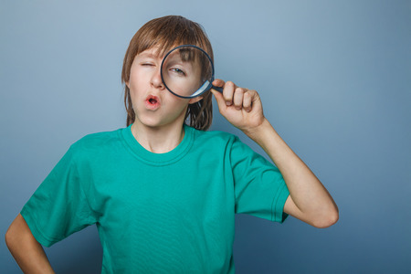 European-looking boy  of ten  years holding a magnifying glass, a keen eye on gray background photo