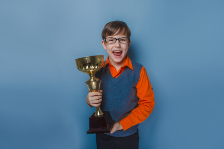 European -looking  boy of  ten years  in glasses holding a cup, award joy on a blue background Stock Photo